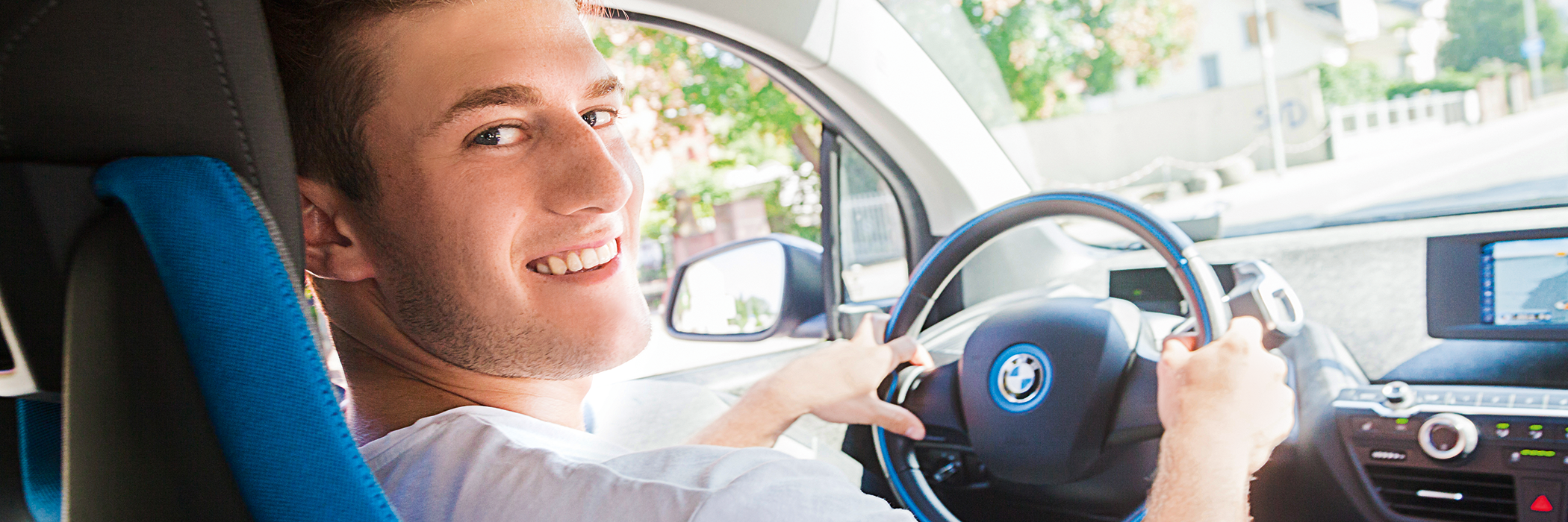 Junger Mann in E-Carsharing Auto.